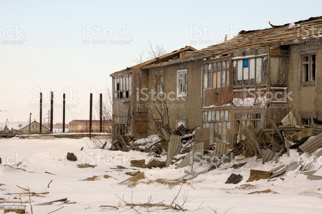 Old two-storied destroyed house in winter with snow around. Poverty and misery, North stock photo