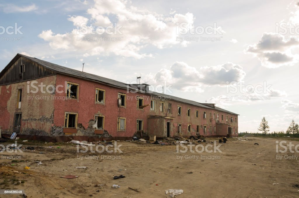 Old two-storied destroyed red house in autumn with sand around. Poverty and misery, North stock photo
