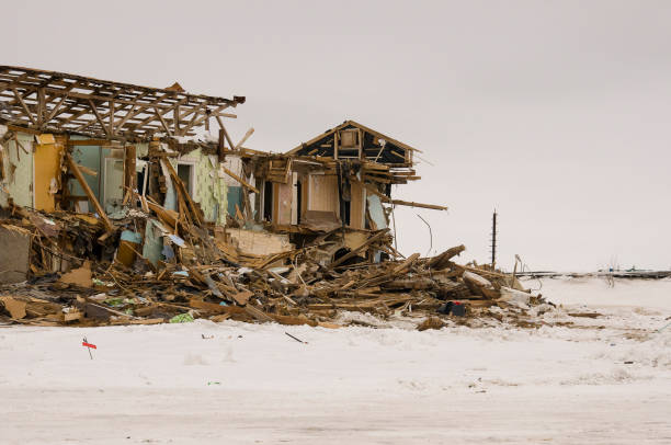 old two-storied destroyed, ruined and desolated house in winter with snow around. poverty and misery, north - desolated stock pictures, royalty-free photos & images