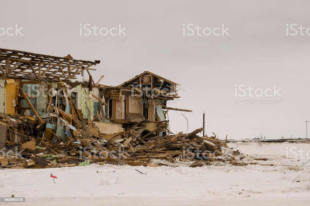 Old two-storied destroyed, ruined and desolated house in winter with snow around. Poverty and misery, North stock photo