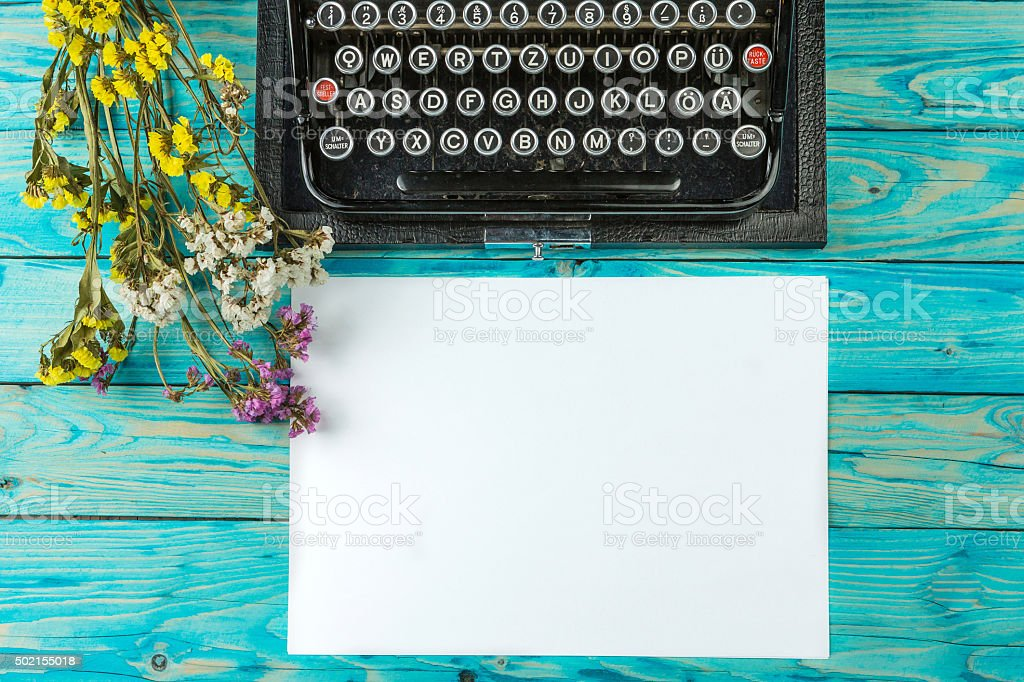 Old typewriter and a blank sheet of paper stock photo