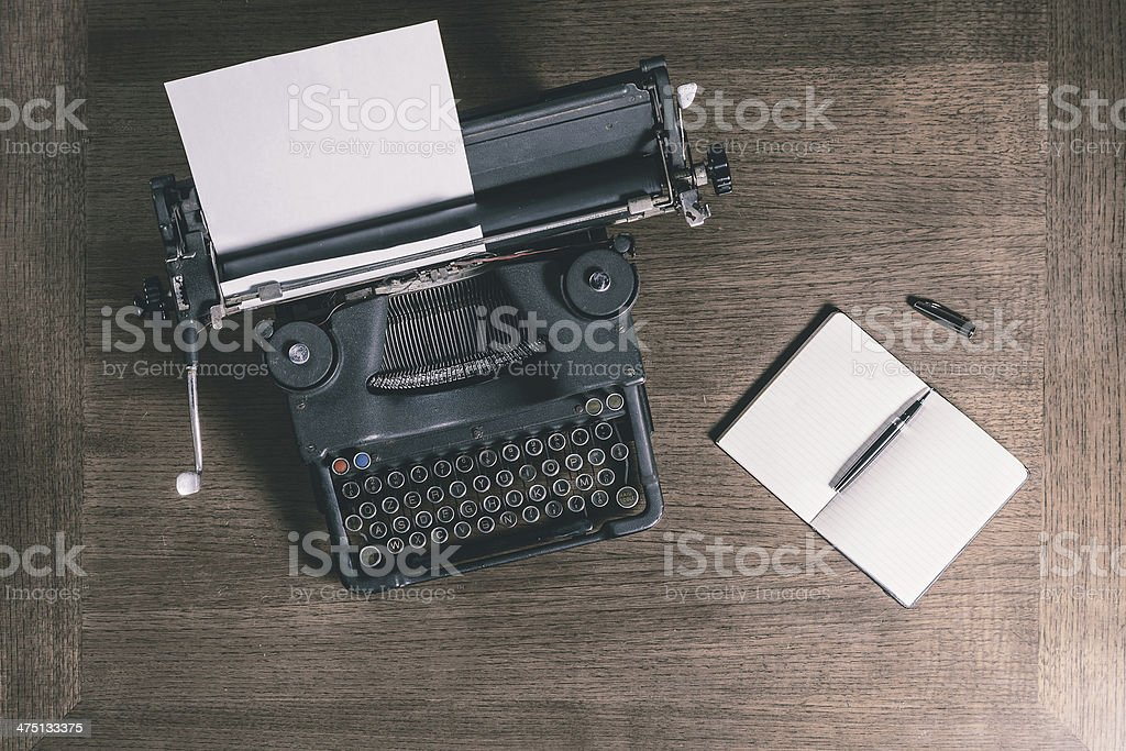 Old typewriter and notebook top view retro style stock photo