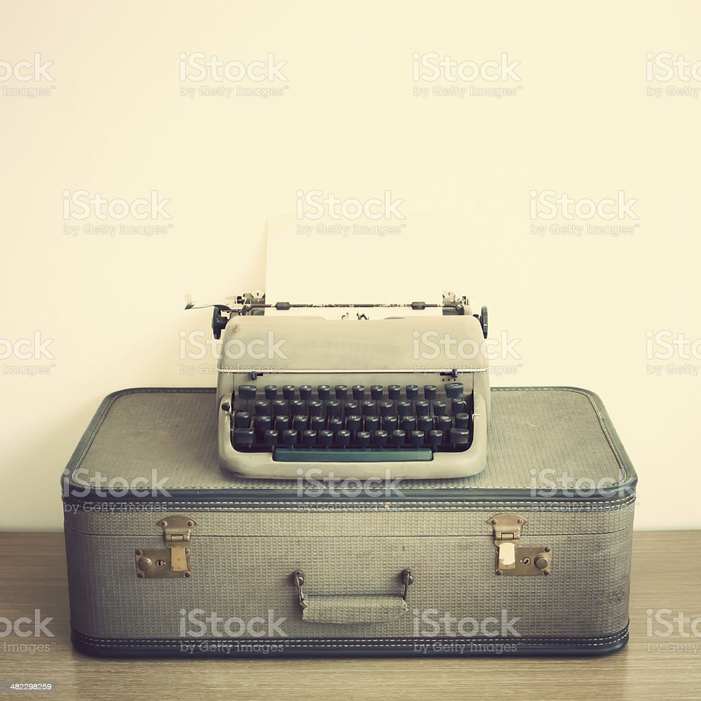 Old typewriter over suitcase stock photo