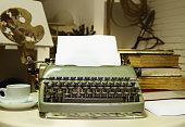 old typewriter with inserted blank sheet of paper on the background of the writer's room