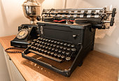 Old typewriter with old phone on the table with lamp  on the background