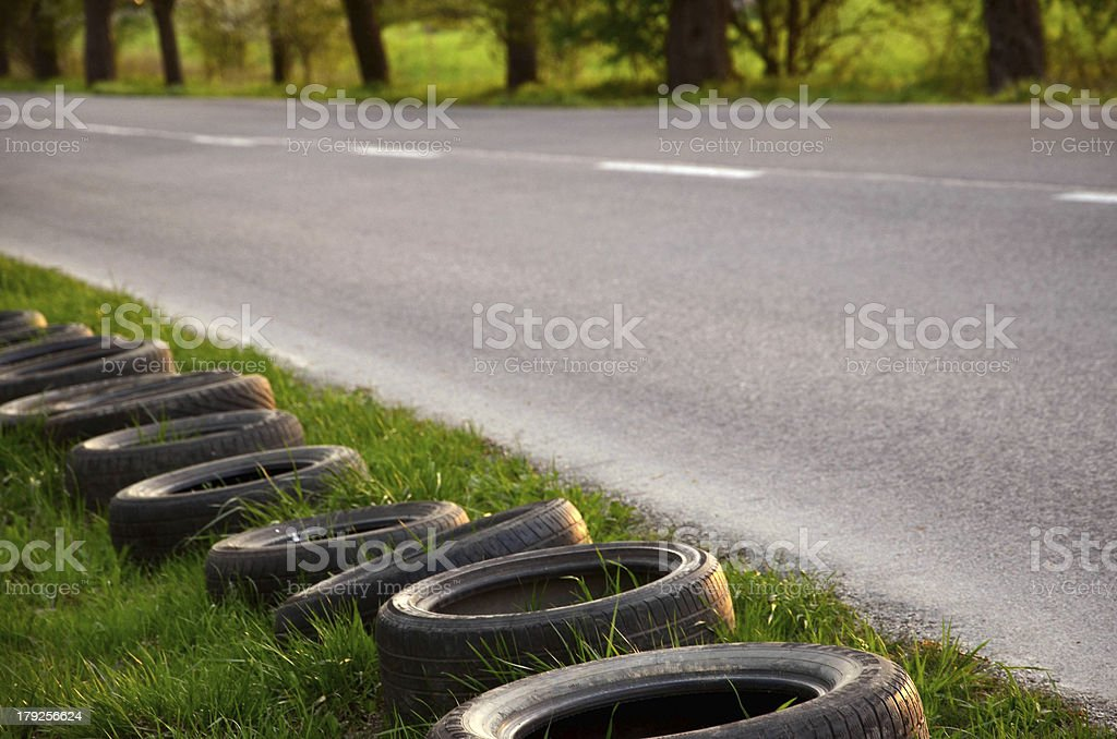 Old tyres are laid next to the empty road. stock photo