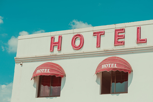Old unclean hotel facade with vintage neon sign