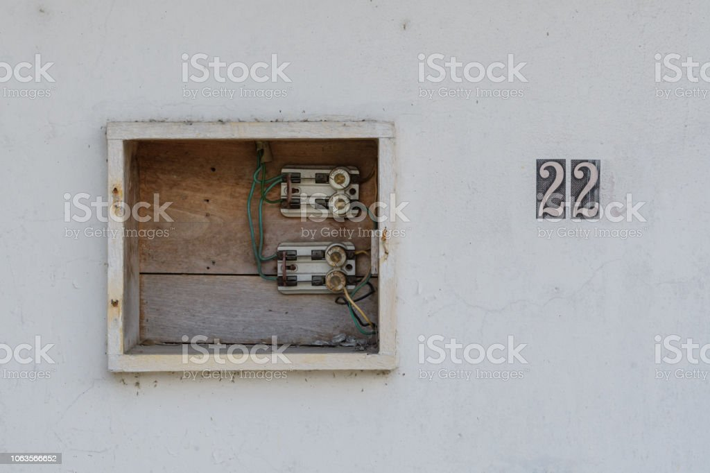 old uncovered wooden fuse box with a house number in mexico - stock image