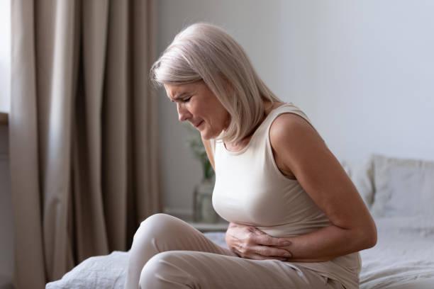 gammal ohälsosam kvinna lider av svår värk buksmärtor - matsmältningsbesvär bildbanksfoton och bilder