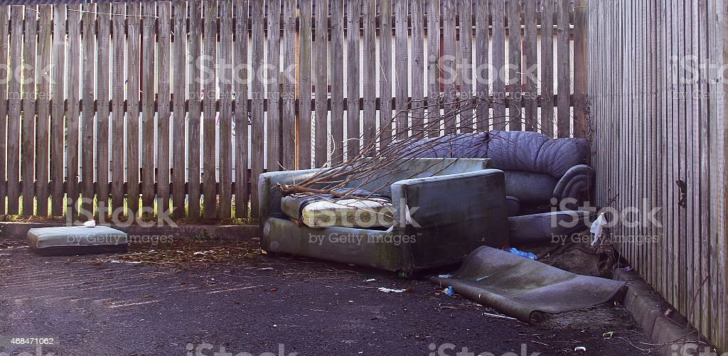 old unwanted sofas in an alley stock photo
