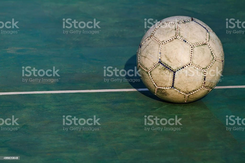 Old used football or soccer ball on cracked asphalt stock photo