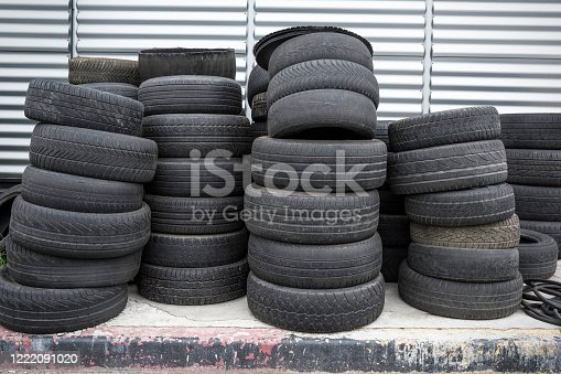 496485590 istock photo Old used tires stacked. Black piles of used tires. 1222091020