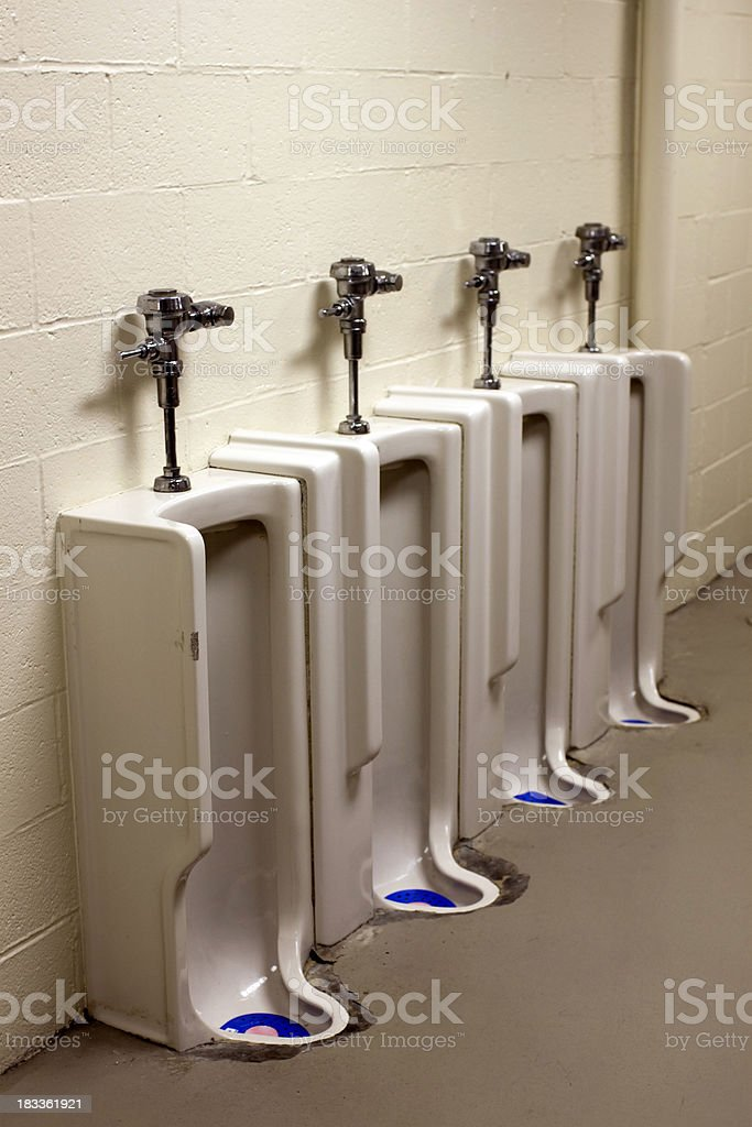 Old utilitarian urinal in bathroom stock photo