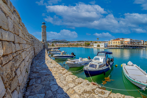 Rethymno, Crete island: The old harbor built by the Venetians in the 13th century, with the Egyptian lighthouse, small fishing boats and yachts, restaurants, taverns, bars and cafes.
