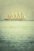 A huge sail vessel sails awayAge, grunge, texture added to the image, to make it look like a vintage picture.
