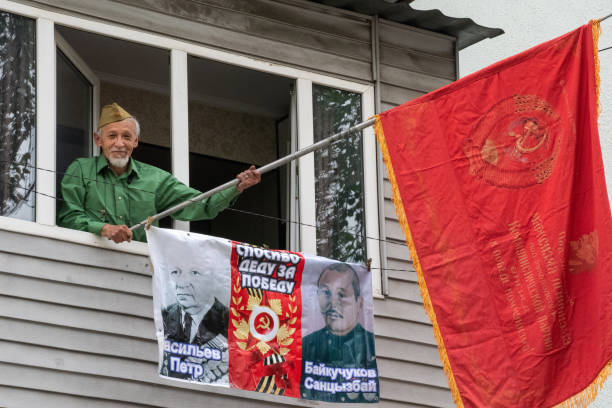 (Editorial) Old veteran is waving Soviet flag from his balcony stock photo