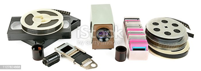 1125303139 istock photo Old videocassettes and video projector with slides isolated on white background. 1127824868