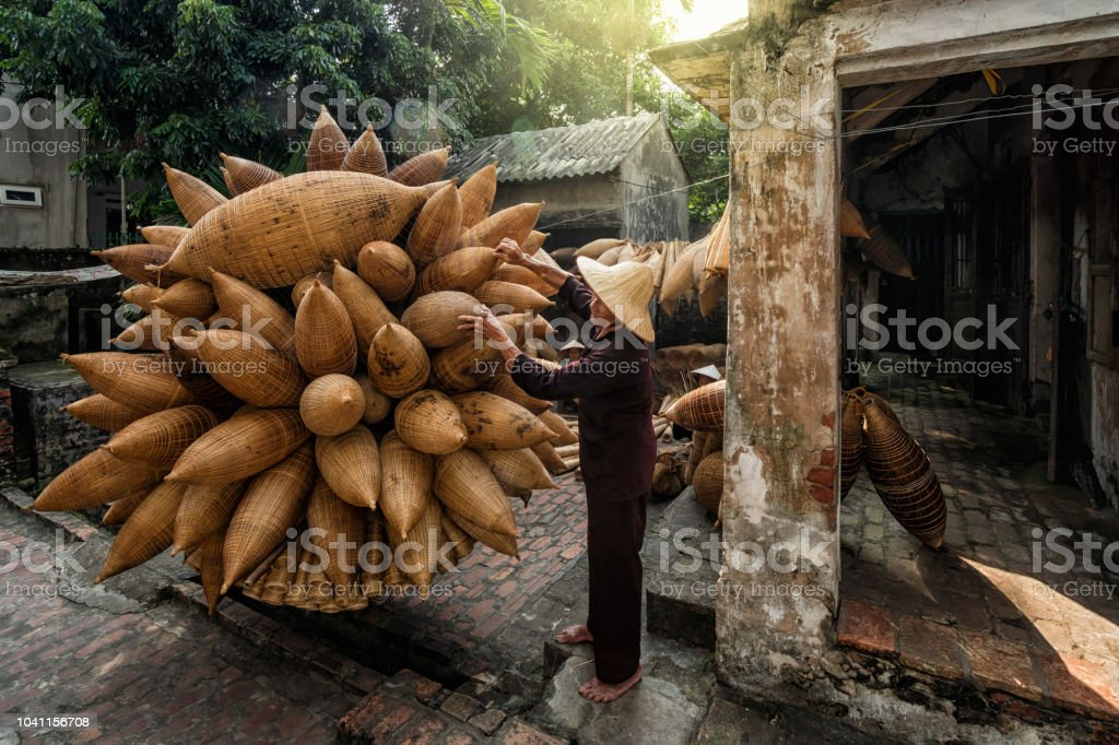 Old Vietnamese male craftsman standing with bicycle which making the traditional bamboo fish trap or weave at the old traditional house in Thu sy village, Hung Yen, Vietnam, traditional artist concept stock photo