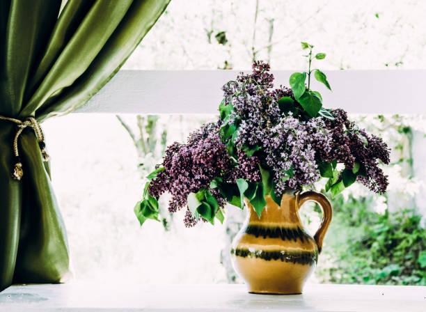 altes dorfhaus. frühlingsgarten und einem bouquet von blühenden flieder auf der fensterbank - küche deko lila stock-fotos und bilder