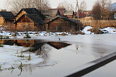 photo of the village with wooden houses. single-storey buildings made of logs.near the river. the time of year is winter. ice water. time of day evening. the sun is setting, the sunset.