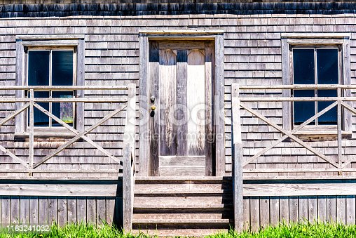Old vintage abandoned wooden house with door porch entrance in idyllic rural countryside in summer