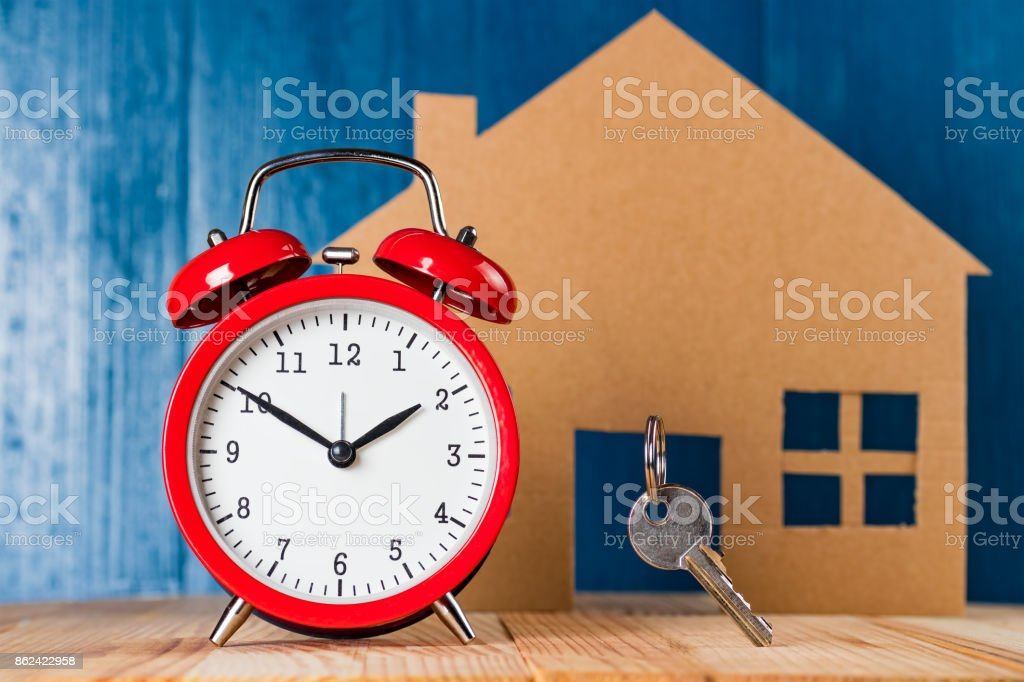 Old vintage alarm clock and door key against house shape. stock photo