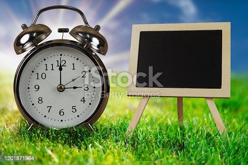 905623256 istock photo Old vintage alarm clock with chalk board. 1201871964
