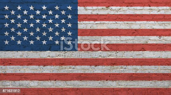 Old grunge vintage American US national flag graffiti over background of white brick wall