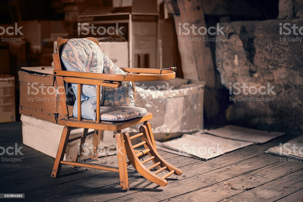 Old vintage baby chair in a dusty attic stock photo