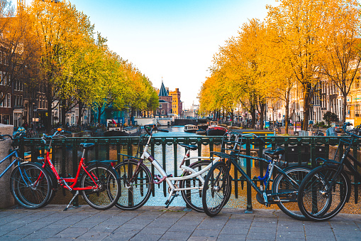 Old vintage bicycles parked on a bridge over the canals of Amsterdam. Amsterdam is the capital and most populous city of the Netherlands in Europe.