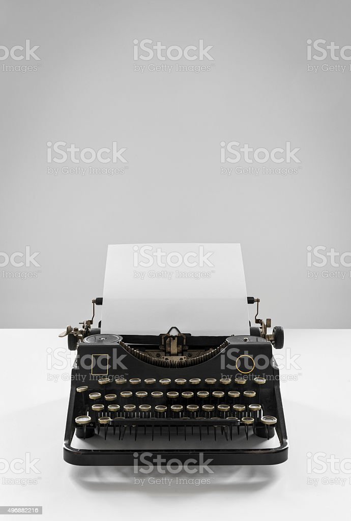 Old vintage black typewriter with empty sheet of paper stock photo