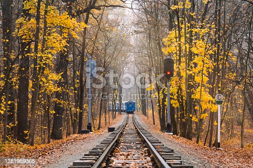 istock Old vintage blue railway train back view on the track rails goes away. Railroad single track through the woods in autumn. Fall landscape. red stop semaphore signal. 1281959365