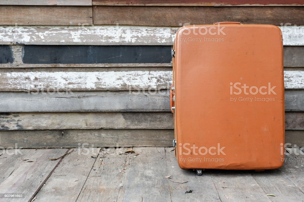 Old vintage brown suitcase on wooden wall stock photo