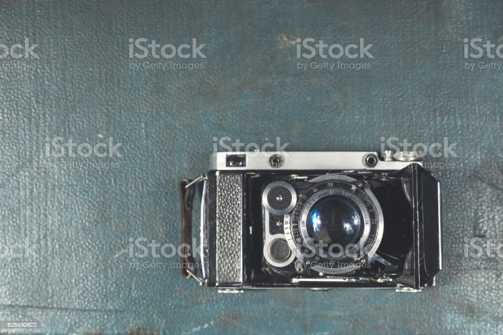 Old vintage camera on a blue scratched background. Focus on the lens stock photo