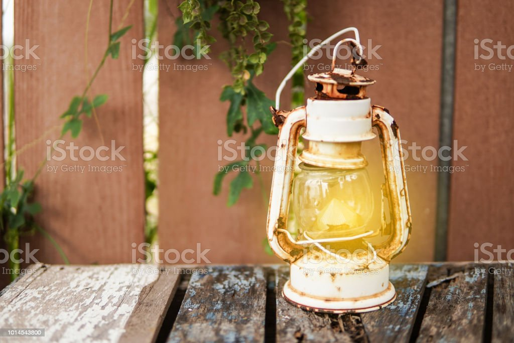Old Vintage Camping Lantern On Wooden Table Retro Gas Lamp With Glowing Fire Wick Stock Photo Download Image Now Istock