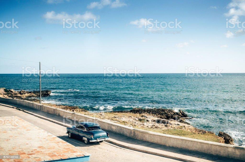 Old vintage car driving along coastline, Cuba stock photo