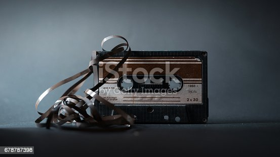 istock Old vintage cassette tape with tangled tape on a dark background 678787398