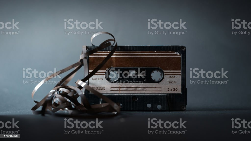 Old vintage cassette tape with tangled tape on a dark background stock photo