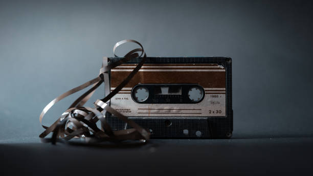 Old vintage cassette tape with tangled tape on a dark background Old vintage cassette tape with tangled tape on a dark background audio cassette stock pictures, royalty-free photos & images