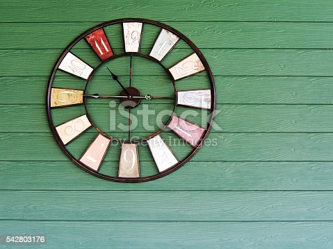 671883446 istock photo Old vintage clock on green wooden plank wall background. 542803176