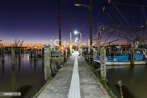 Old vintage dock were tired shrimp boats wait to go to work on calm water with deep purple and orange sunset of clear sky
