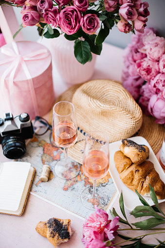 old vintage film camera, paper notebook, world map, hat, croissants, pink peonies, roses in a vase, velvet pink gift box and a bottle of rose wine with two glasses on the pink wooden table