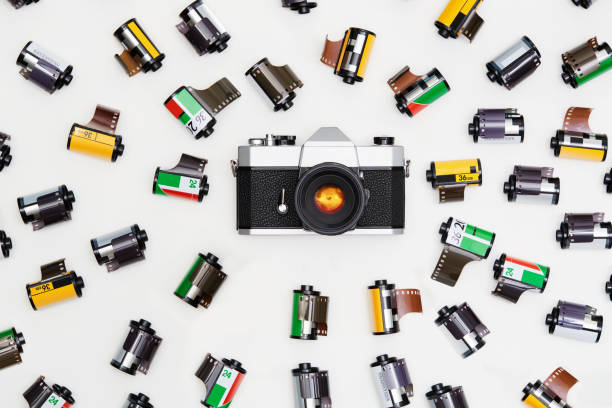 Old vintage film camera with lots of film canisters on white background from above stock photo