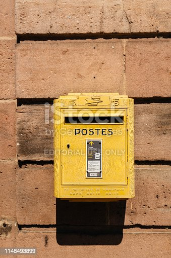 istock Old vintage French La Poste mailbox painted in yellow 1148493899