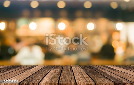 istock old vintage grungy brown wood panel tabletop with blurred restaurant bar cafe light color background for show,promote and advertise product on display 1053337334