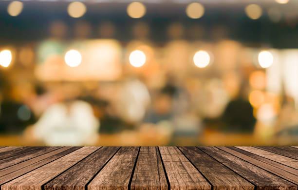 alte vintage grunge braune holzplatte tischplatte mit unscharfen restaurant bar café lichtfarbe hintergrund für show, förderung und werbung produkt auf dem display - tresentisch stock-fotos und bilder