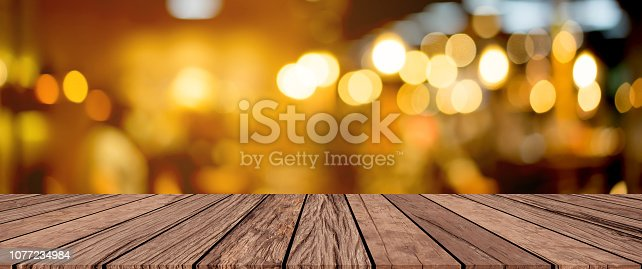 istock old vintage grungy brown wood panel tabletop with blurred restaurant bar cafe light color background for show,promote and advertise product on display 1077234984
