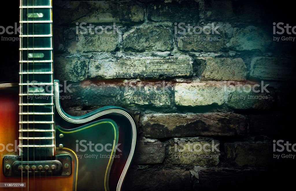 Old Vintage Jazz Guitar On A Brick Wall Background Copy