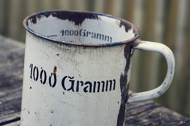 old vintage metallic cup for 1000 grams with  wooden background - pfannen test stock-fotos und bilder
