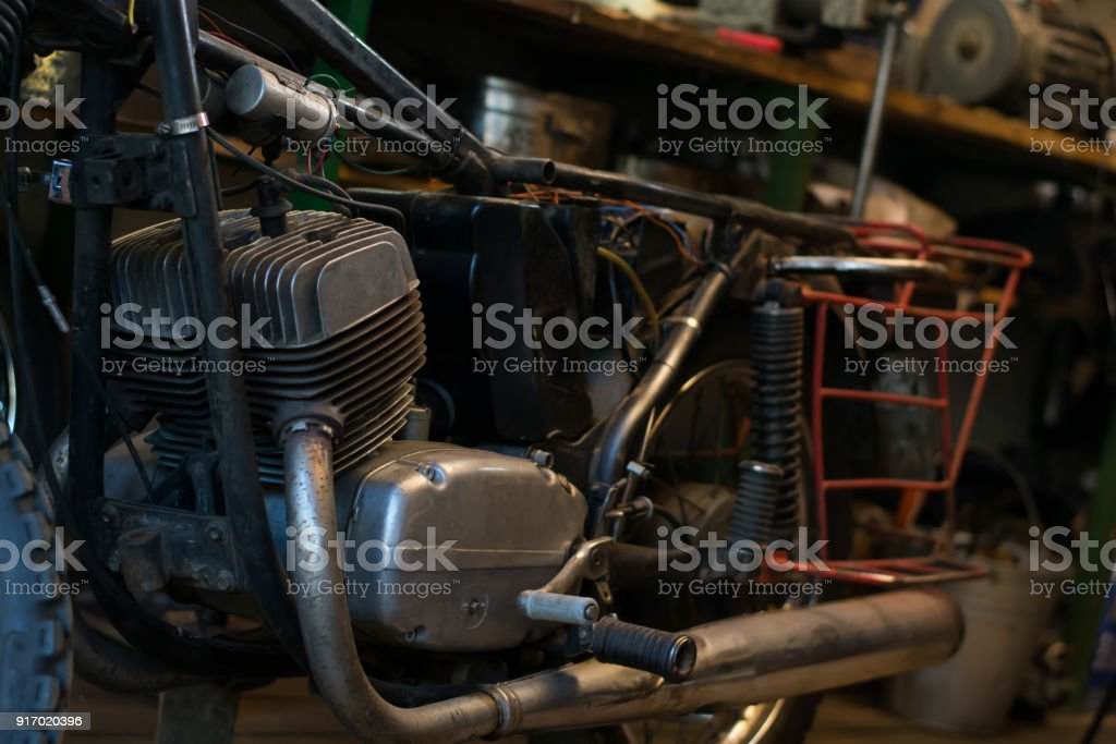 Old vintage motorcycle, which needs to be repaired, in the workshop stock photo